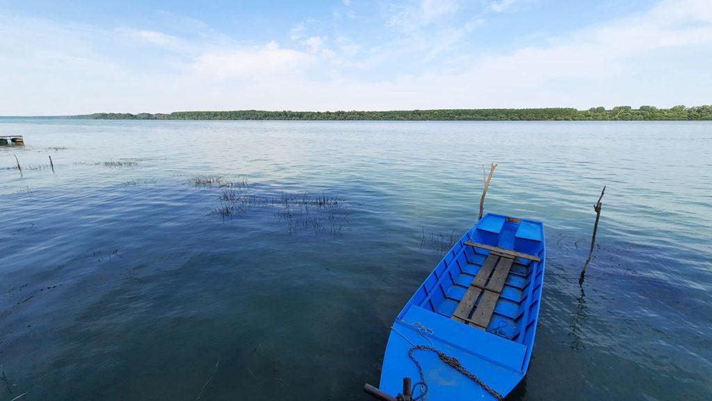 mirna reka na kojoj je ukotvljen plavi čamac