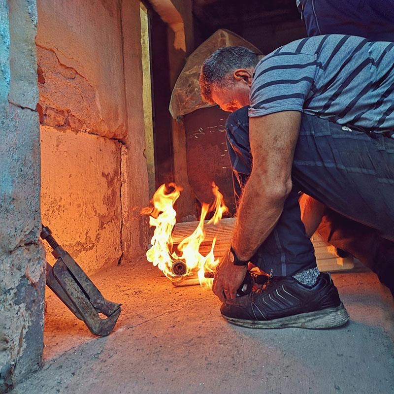 čovek koji nešto radi nad vatrom