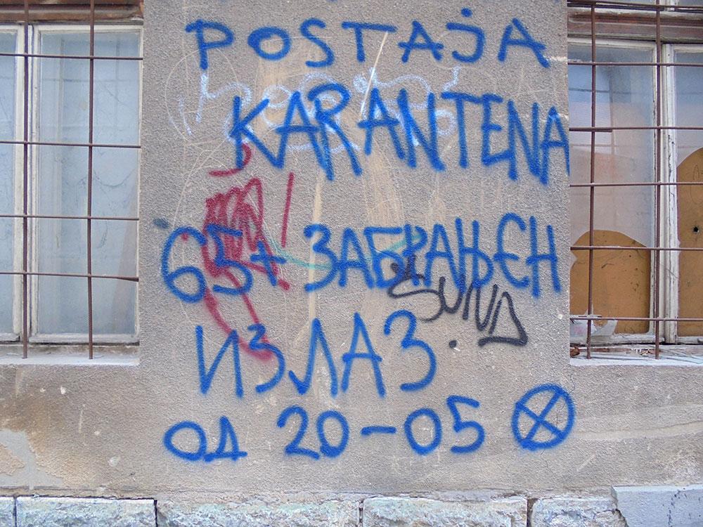 Natpis sprejem na zidu: Postaja karantena 65+ zabranjen izlaz od 20-05