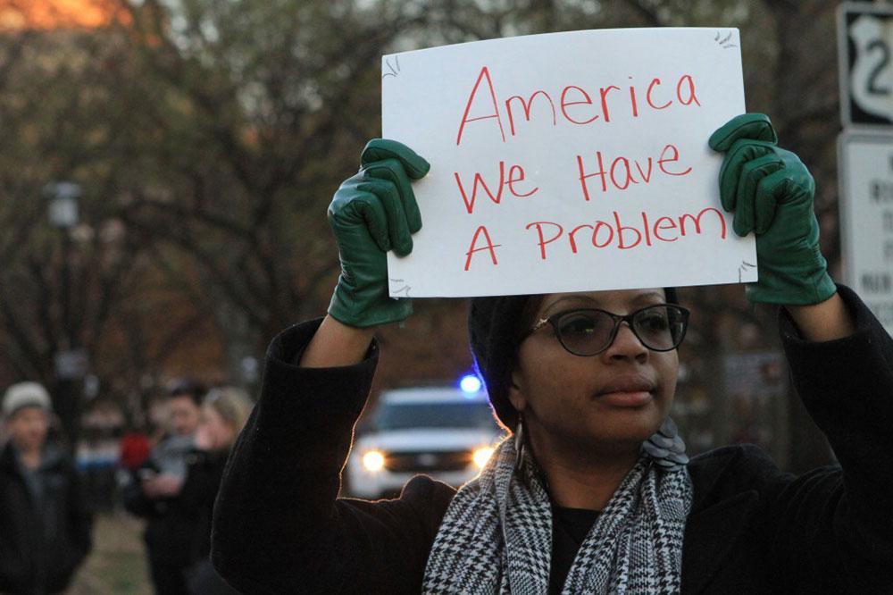 Žena drži transparent: America we have a problem