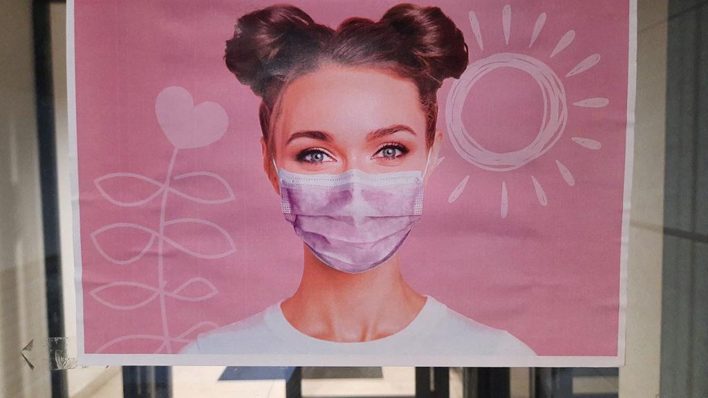 bilbord sa devojkom koja ima zaštitnu masku na licu