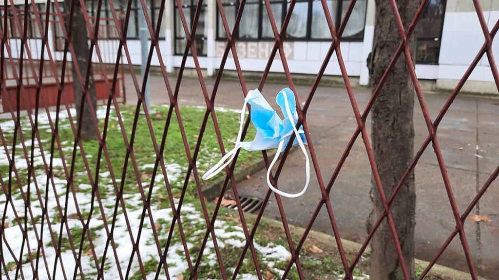 zaštitna maska za lice ostavljena na ogradi