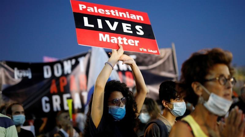 Protesti u Tel Avivu, jun 2020, žena drži transparent: Palestinian Lives Matter