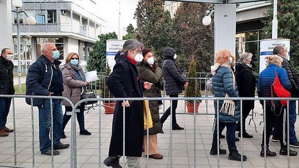 ljudi čekaju uredu za vakcinaciju