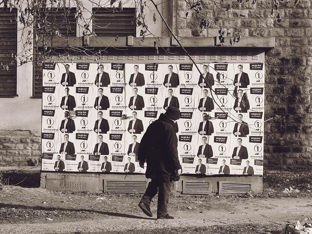 Čovek prolazi ispred plakata sa likom AV