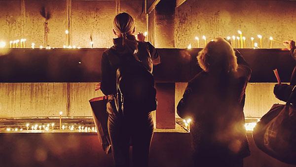 žene pale sveće u crkvi