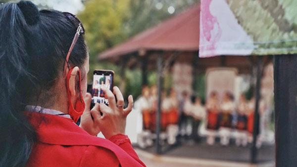 devojka fotografiše mobilnim telefonom
