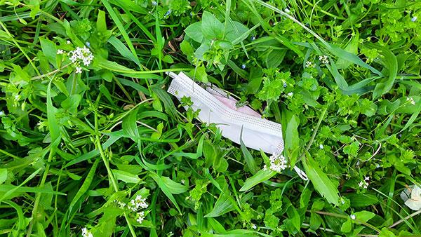 maska za lice bačena u travu