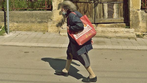 starica sa maskom na licu hoda ulicom