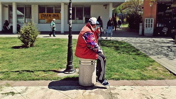 čovek sedi na kanti za smeće