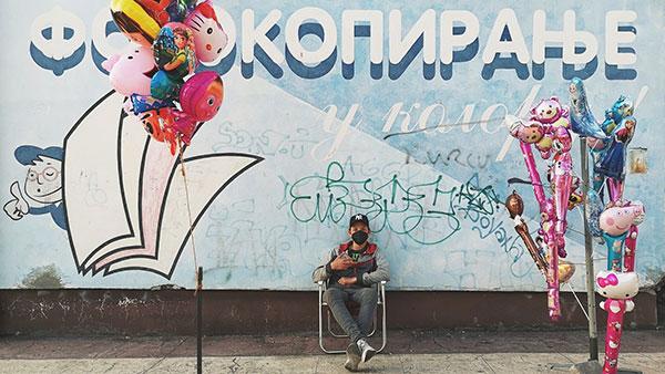 dečak sa maskom na licu prodaje balone