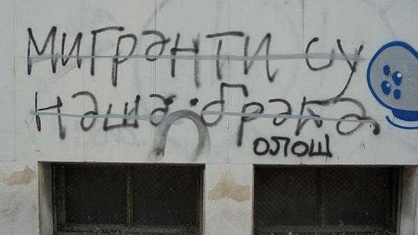 Precrtan grafit na kojem piše: Migranti su naša braća, i ispod njega dopisano Ološ