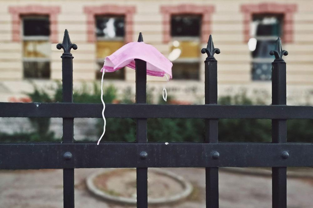 zaštitna maska za lice nakačena na ogradu
