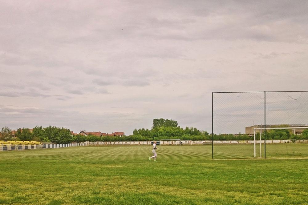žena trči oko fudbalskog terena