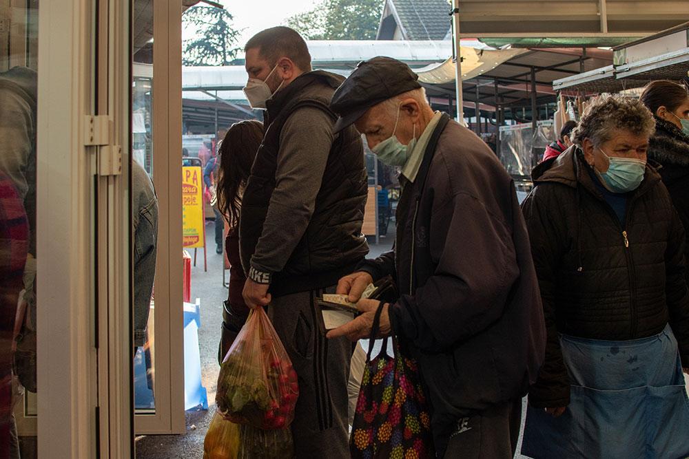 ljudi sa maskama čekaju u redu ispred prodavnice