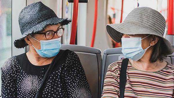 dve žene u autobusu sa maskama na licu