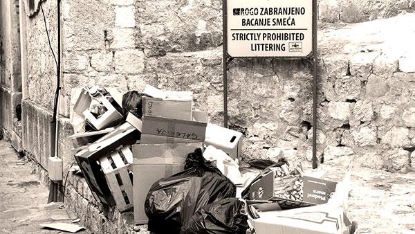 Tabla: Strogo zabranjeno bacanje smeća, ispred koje je bačeno smeće