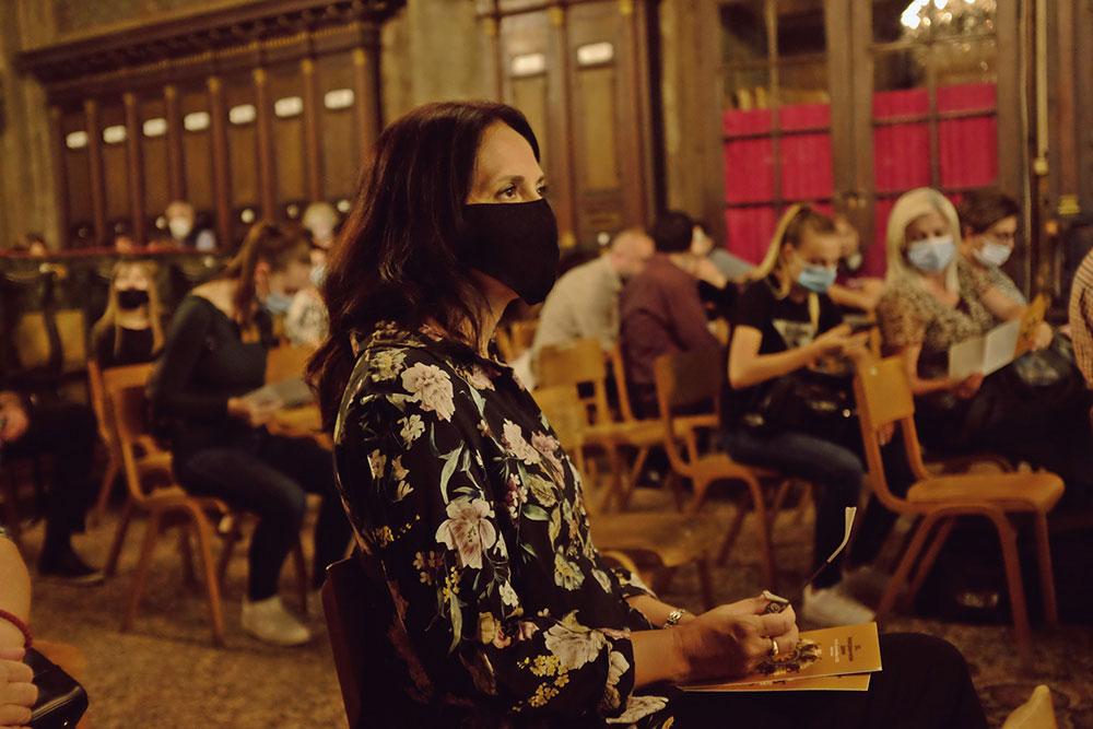 žena sa maskom na licu u koncertnoj sali